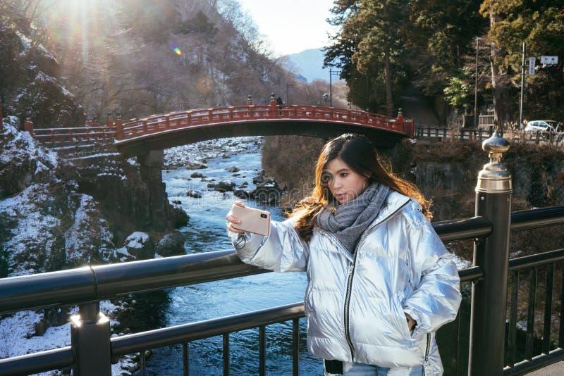 Tourist woman selfie by Smartphone with  Shinkyo Bridge, Nikko, Japan in Winter stock images