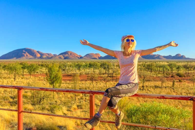 Tourist woman in Australian Outback. Tourist woman sitting on the balcony from dune viewing area enjoys Mount Olga rock formation in Uluru-Kata Tjuta National royalty free stock images