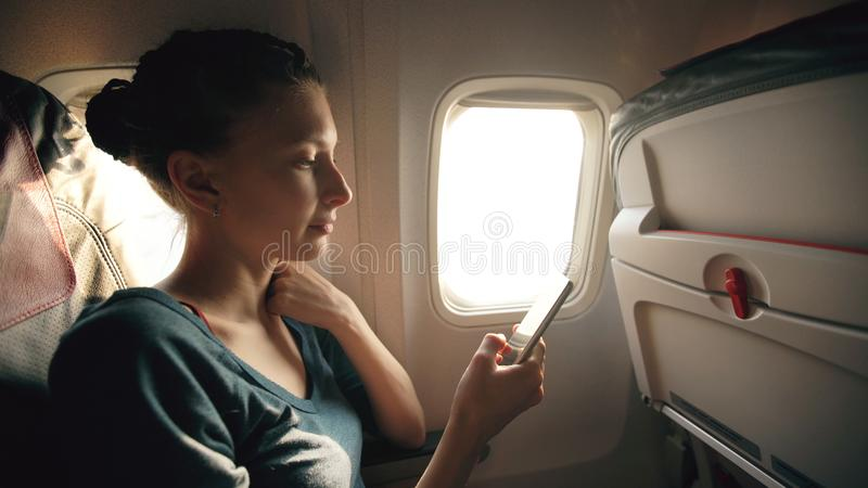 Tourist woman sitting near airplane window at sunset and using mobile phone during flight royalty free stock image