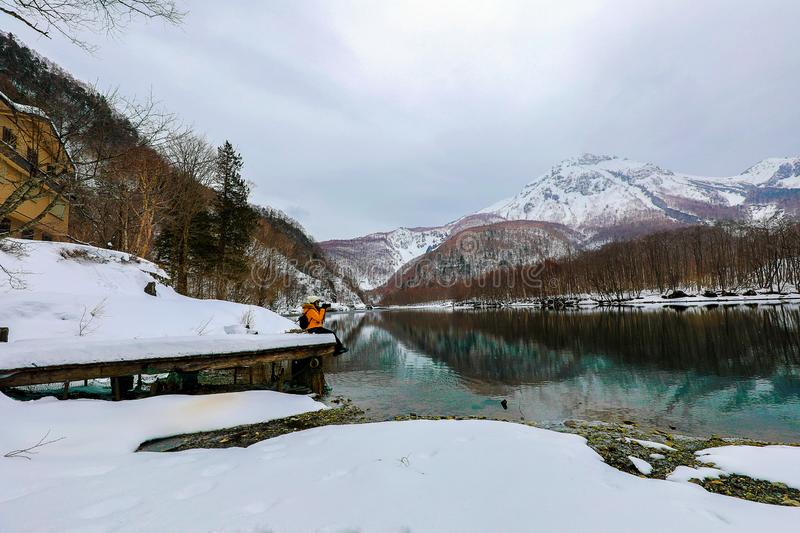 Tourist woman in the snow mountain with rivers at the Kamikochi in Japan Alps Mountain. Winter season concept stock image