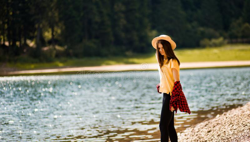 Tourist woman in straw hat rest near turquoise blue lake and scenic landscape. stock images
