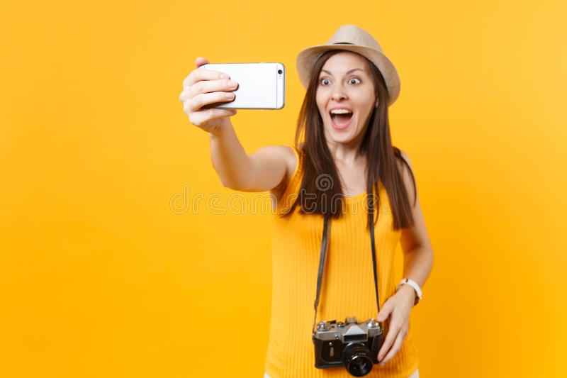 Tourist woman in summer casual clothes, hat doing taking selfie shot on mobile phone isolated on yellow background royalty free stock photos