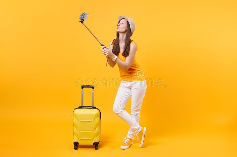 Tourist woman in summer casual clothes, hat doing taking selfie shot on mobile phone isolated on yellow orange royalty free stock images