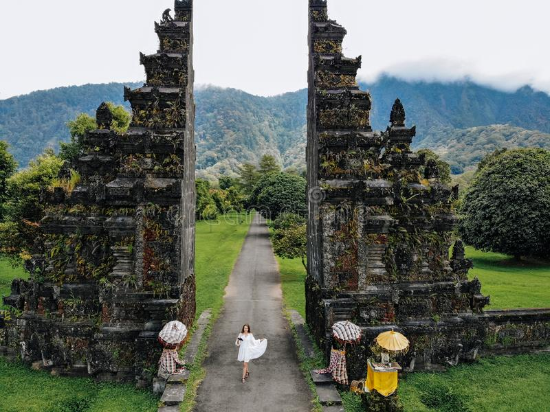 Tourist woman take a photo of yourself with drone near Traditional Balinese Hindu gate Candi Bentar close to Bedugul stock photography