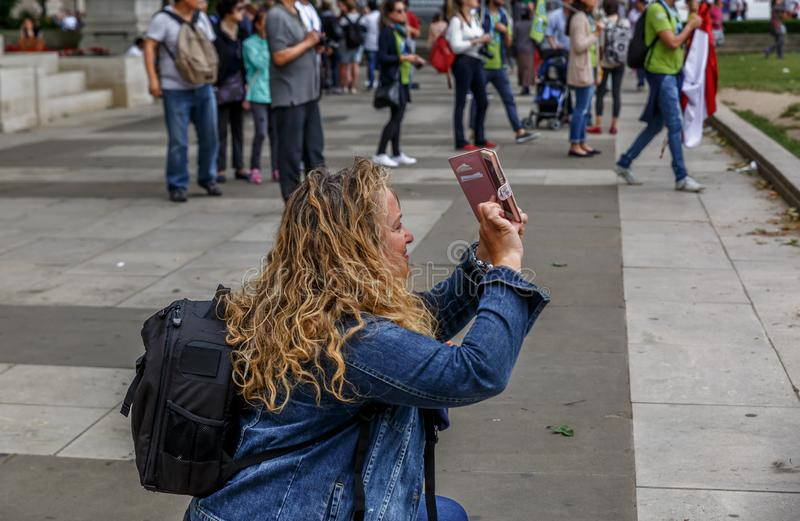 A tourist woman takes pictures with her mobile phone on a busy street in London stock photography