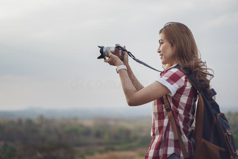 Tourist woman taking photo with her camera in nature. Tourist woman taking a photo with her camera in nature royalty free stock image