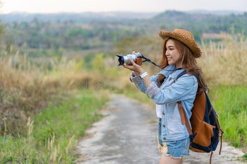 Tourist woman taking photo with her camera in nature. Tourist woman taking a photo with her camera in nature royalty free stock photography