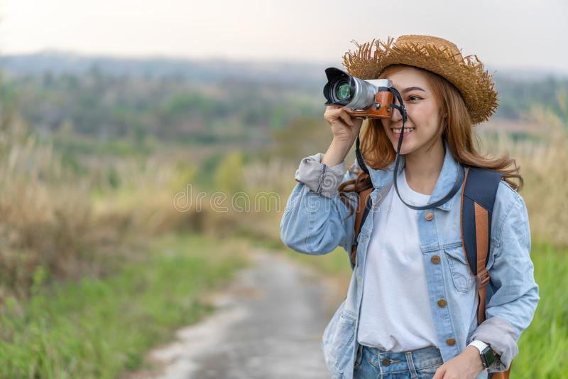 Tourist woman taking photo with her camera in nature. Tourist woman taking a photo with her camera in nature royalty free stock photo