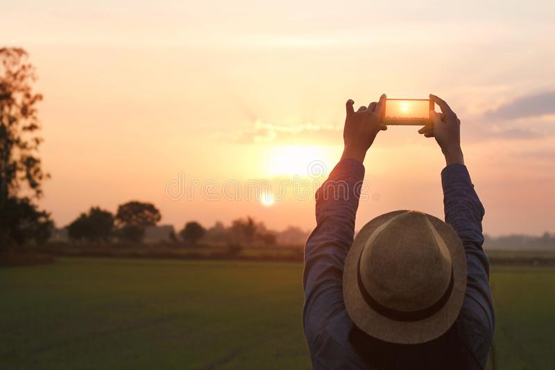 Tourist woman taking photo with smartphone on sunset nature ba royalty free stock photo