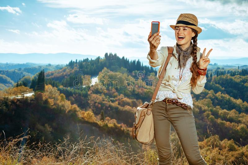 Tourist woman taking selfie with phone and showing victory. Happy fit tourist woman in hiking gear with bag taking selfie with phone and showing victory gesture stock image