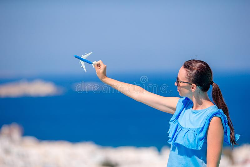 Tourist woman with toy airplane in hands background the old greek village. Tourist beautiful woman with toy airplane in hands background the old greek village stock photos
