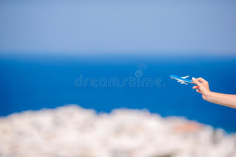 Tourist woman with toy airplane in hands background the old greek village. Closeup toy airplane in hands background the old greek village and blue sea stock photo