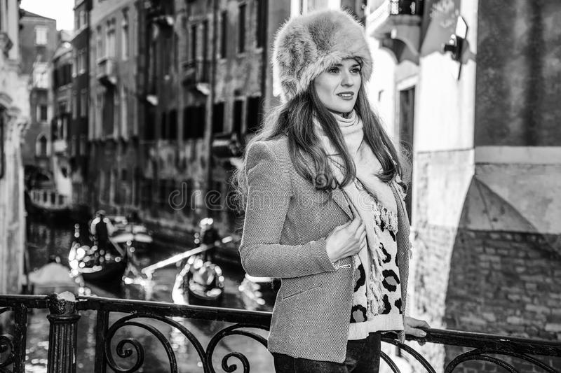 Tourist woman in Venice, Italy in winter looking into distance. Venice. Off the Beaten Path. modern tourist woman in fur hat in Venice, Italy in the winter stock images