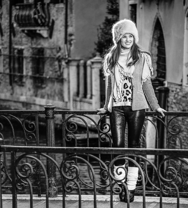 Tourist woman in Venice, Italy in winter looking into distance. Venice. Off the Beaten Path. Full length portrait of smiling trendy tourist woman in fur hat in royalty free stock images