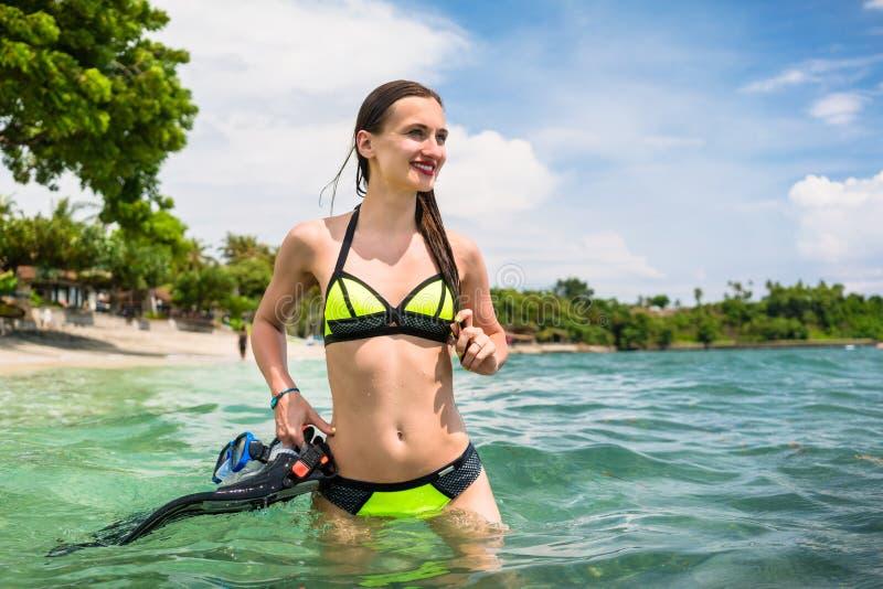 Woman holding snorkelling equipment, standing in sea. Tourist woman wearing bikini holding snorkelling equipment, standing in sea royalty free stock photo