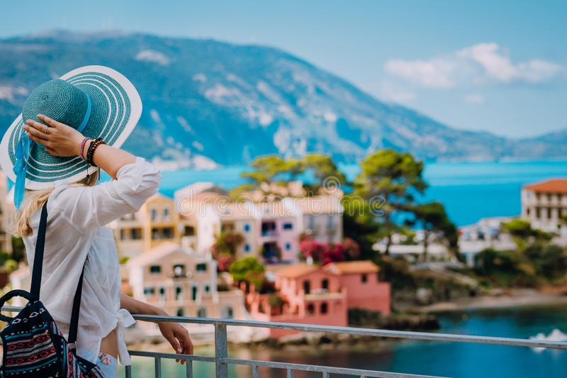 Tourist woman wearing blue sunhat and white clothes enjoying view of colorful tranquil village Assos on sunny day stock photography