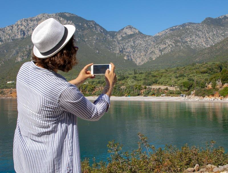 Tourist woman with white hat takes a picture of the of the Agia Kyriaki beach in the Kiparissi Lakonia village, Peloponnese, stock photos