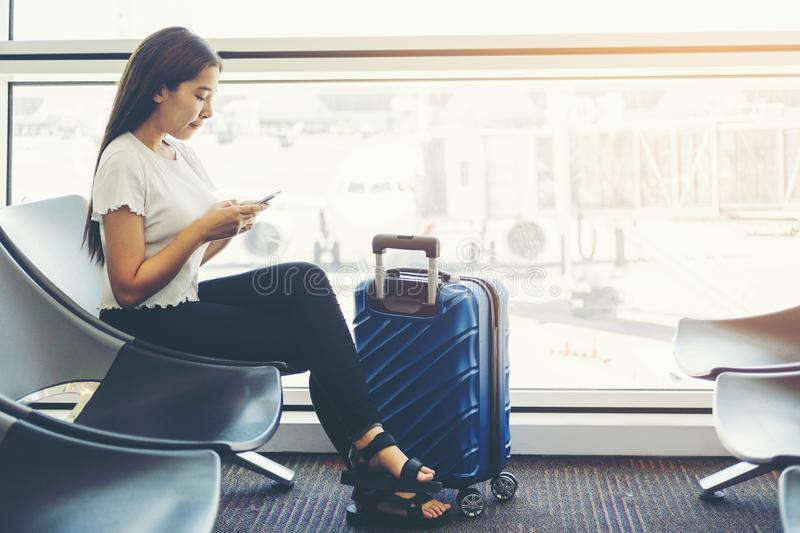Tourist Women using Phone at international airport waiting for boarding royalty free stock images