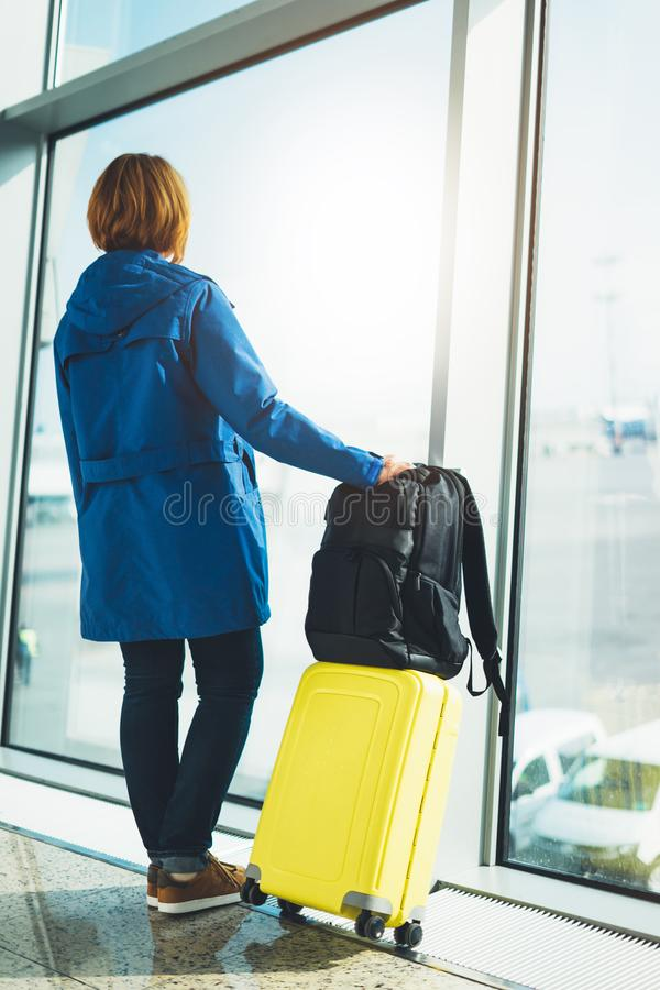 Tourist with yellow suitcase backpack is standing at airport on background large window, traveler girl waiting in departure lounge. Area hall of royalty free stock photography