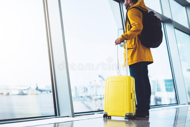Tourist with yellow suitcase backpack is standing at airport on background large window, traveler man waiting in departure lounge. Area hall of  stock image