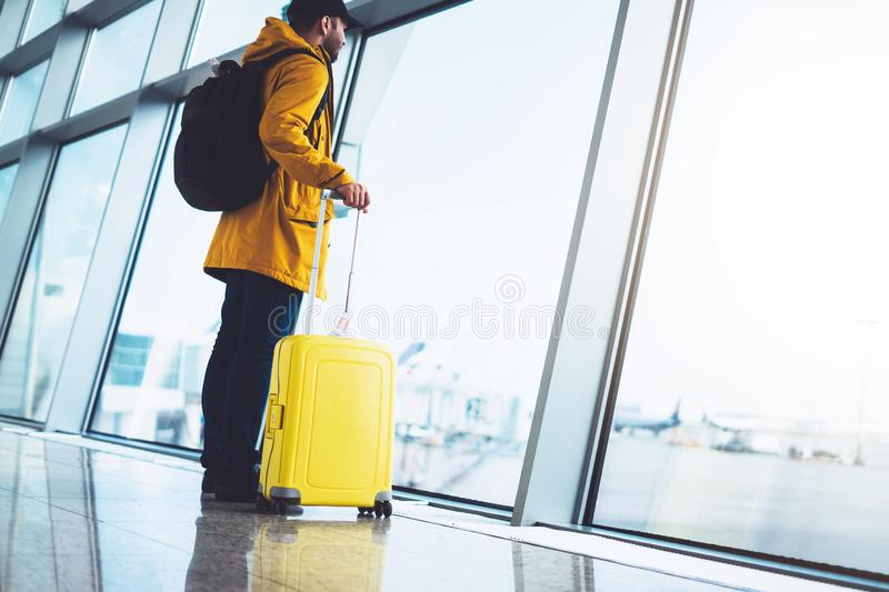 Tourist with yellow suitcase backpack is standing at airport on background large window, traveler person waiting in departure loun. Ge area hall of stock photo
