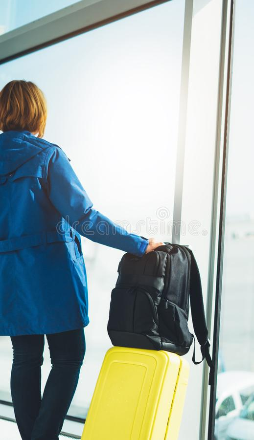 Tourist with yellow suitcase backpack is standing at airport on background large window, traveler woman waiting in departure loung. E area hall of stock image