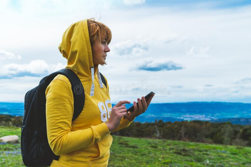 Tourist young girl looks distance on background mount using mobile smartphone, women holding in female hands gadget technology. Tourist young girl looks distance stock image
