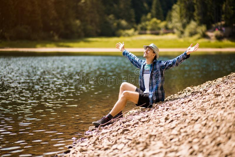 Tourist young man walking on the forest lake beach in summer. stock images