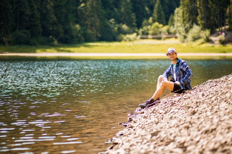 Tourist young man walking on the forest lake beach in summer. stock image