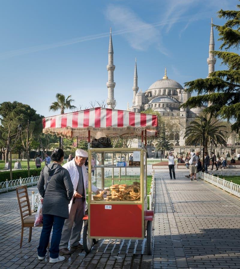 Touriste achetant le repas de rapide d'un chariot turc de bagel de Simit de turc traditionnel en Sultan Ahmed Square, Istanbul, T images stock