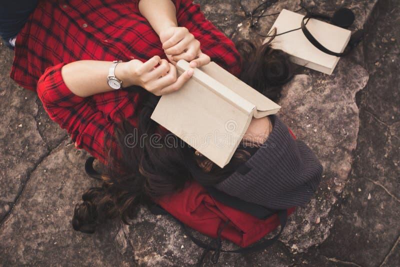 Touriste asiatique de détente de moment lisant un livre sur la roche photos libres de droits