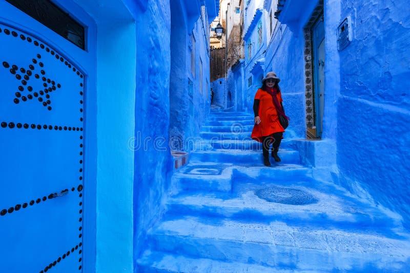 Touriste asiatique de femme dans la robe rouge marchant sur une rue en Médina de Chefchaouen image stock