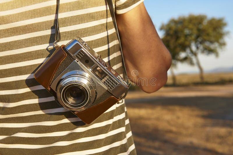 Touriste avec l'appareil-photo de vintage dans la campagne Backgroun de voyage photographie stock libre de droits