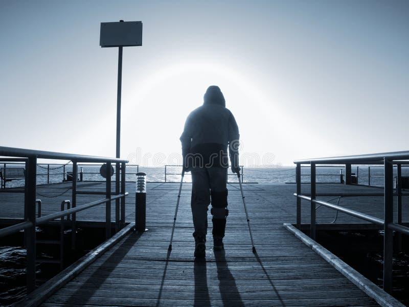 Touriste avec la promenade de jambe cassée avec des béquilles sur le pont photographie stock libre de droits