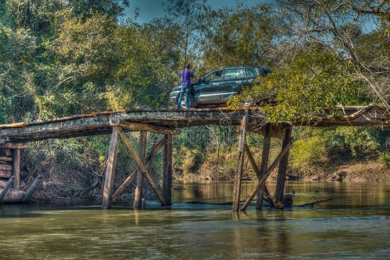 Touriste avec la voiture sur un grand, délabré pont en bois dans la région sauvage du Paraguay photographie stock