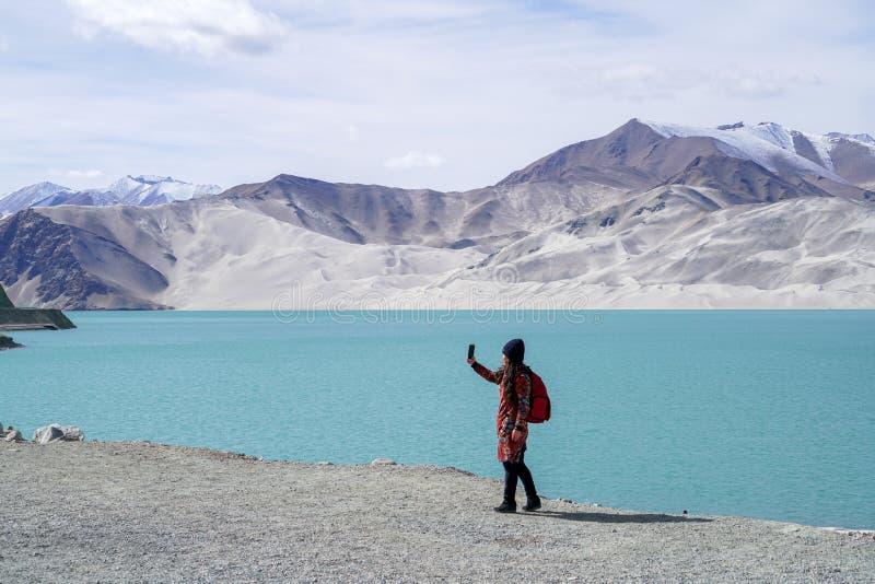 Touriste avec le lac vert, montagne de neige, nuages blancs, ciel bleu photo libre de droits