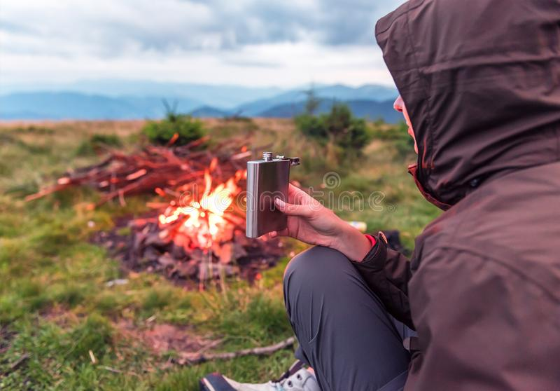 Touriste avec un flacon près du feu image stock