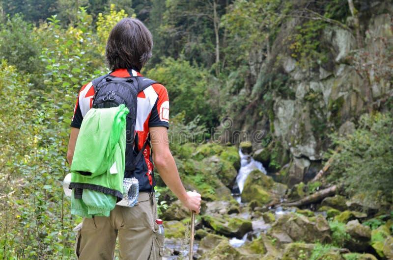 Touriste d'homme dans des vêtements lumineux avec une position de bâton sur la montagne, regardant la cascade et les montagnes en photo libre de droits