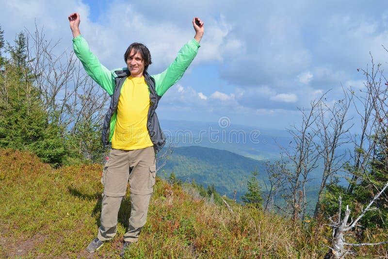 Touriste d'homme dans la veste et le pantalon se tenant sur la montagne, soulevant ses mains et heureux montagnes, nuages à l'arr image stock