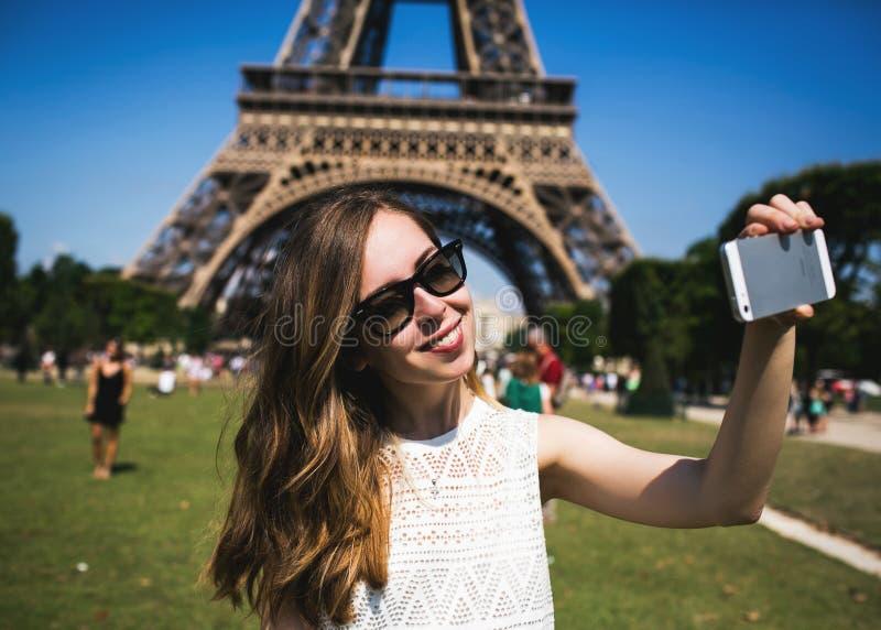 Touriste de femme à Tour Eiffel souriant et faisant photographie stock libre de droits
