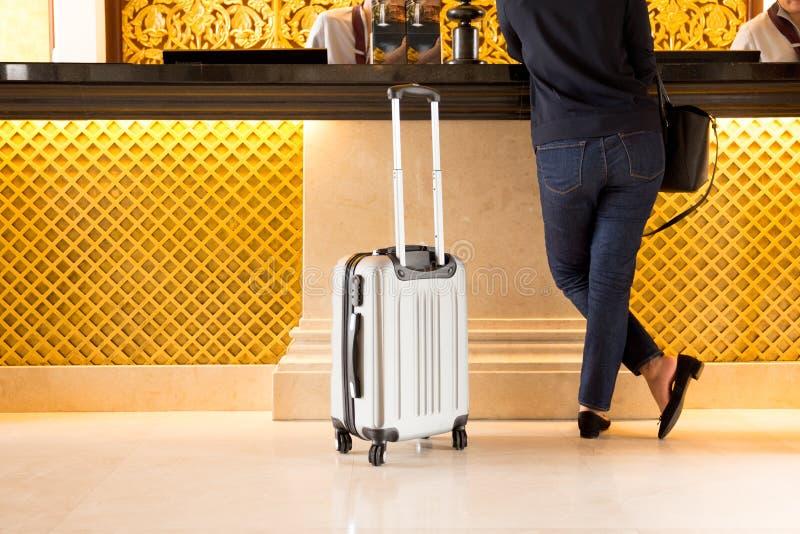 Touriste de femme avec le chek de valise dedans à la réception images stock