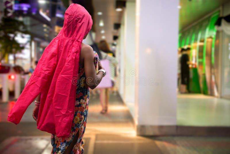 Touriste de femme en tissu imperméable rouge marchant sur la route images libres de droits
