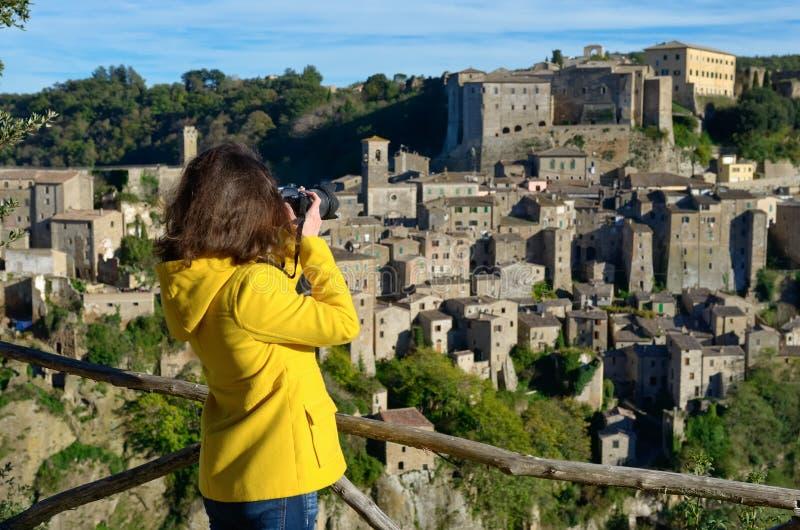 Touriste de femme faisant la photo de la ville médiévale de Sorano de tuf en Italie images stock
