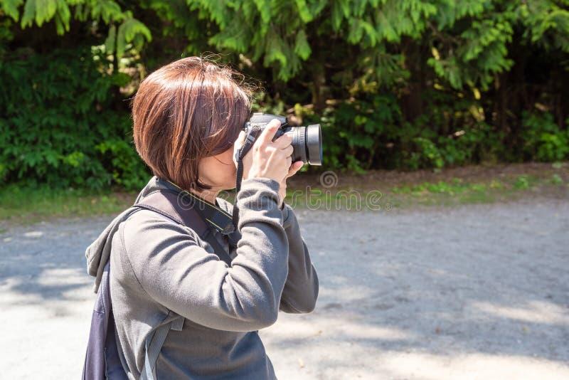 Touriste de femme prenant des photos avec sa caméra extérieure photo libre de droits
