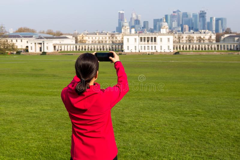 Touriste de femme prenant des photos du bâtiment en parc avec le téléphone portable image stock