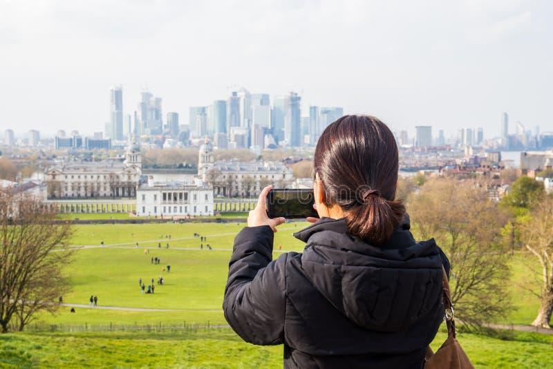 Touriste de femme prenant des photos en parc avec la ville bulding à l'arrière-plan images stock