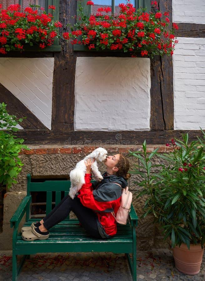 Touriste de fille embrassant le chien maltais de bichon en Allemagne photos stock
