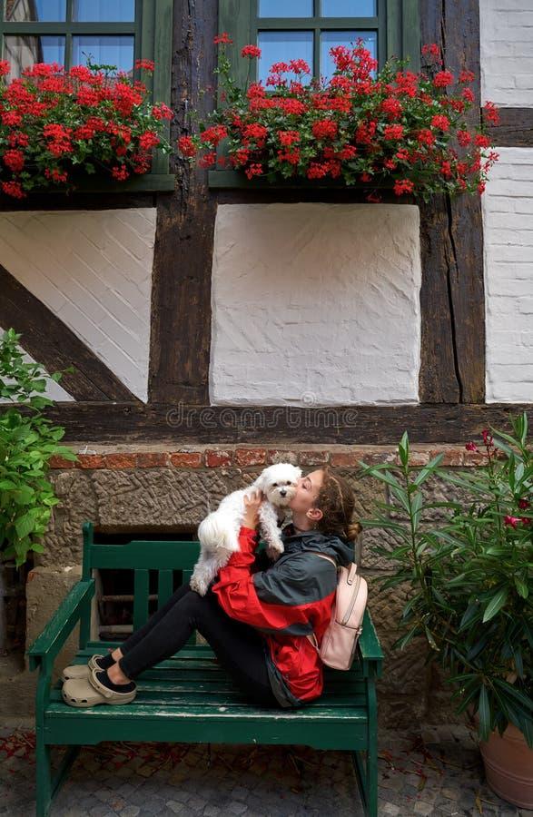 Touriste de fille embrassant le chien maltais de bichon en Allemagne images stock