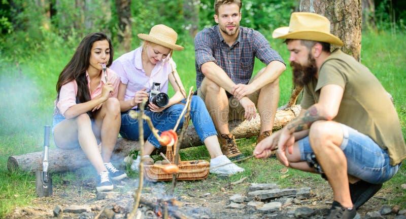 Touriste de groupe d'amis détendant près du feu Saucisse de torréfaction de hippie tandis qu'amis parlant partageant l'impression photos stock
