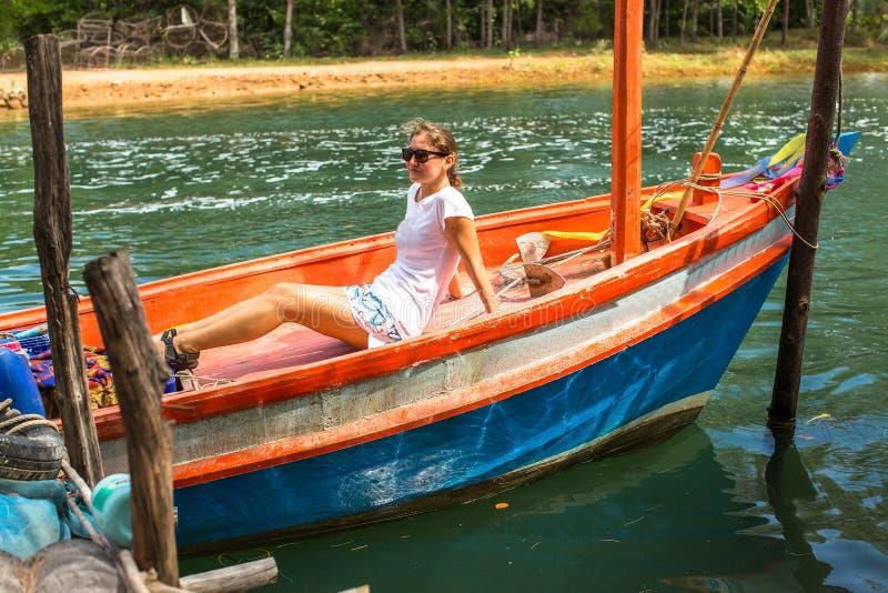 Touriste de jeune fille s'asseyant dans un bateau de pêche thaïlandais nature photo libre de droits